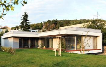 Pohľad zo záhrady, umiestnenie domu na pozemku umožnilo použiť bohaté presklenie smerom do záhrady. Prestrešnie terasy pred obývačkou je hlboké takmer 3m, takže terasa je chránená nielen pred slnkom ale aj pred dažďom.
