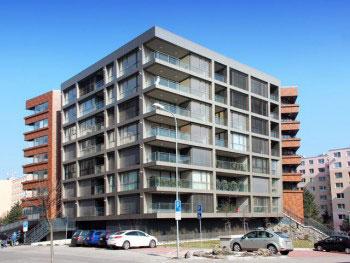 Autori: Ľubomír Novák, Jozef Ondriaš, Ondrej Ondriaš. Celkový pohľad z juhozápadu na zrealizovaný bytový dom. Slnečná orientácia s presklennými stenami.